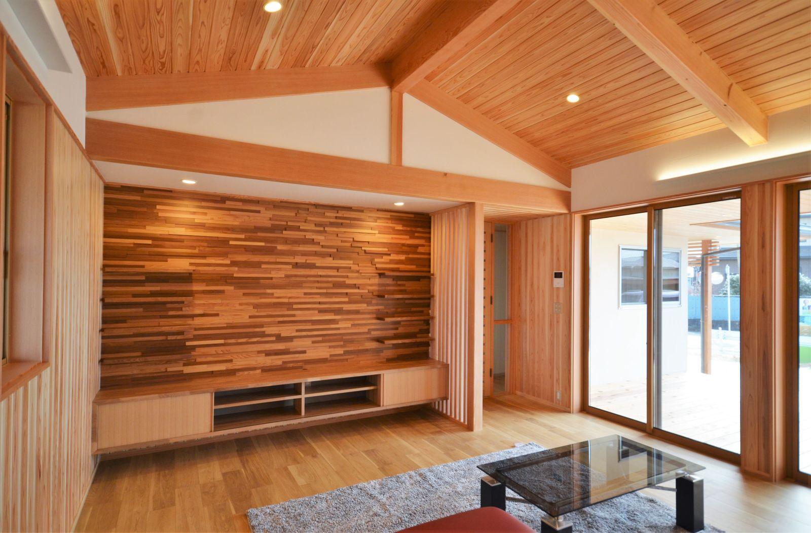 木製デッキ越しに庭をのぞむ平屋の家